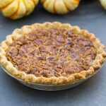Simple pecan pie topped with pieces of pecans in glass pie dish sitting on gray slate surface with small pumpkins in background