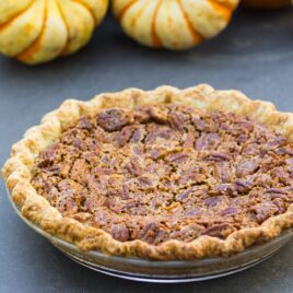 Simple pecan pie in glass pie dish sitting on gray slate surface with small pumpkins sitting in background