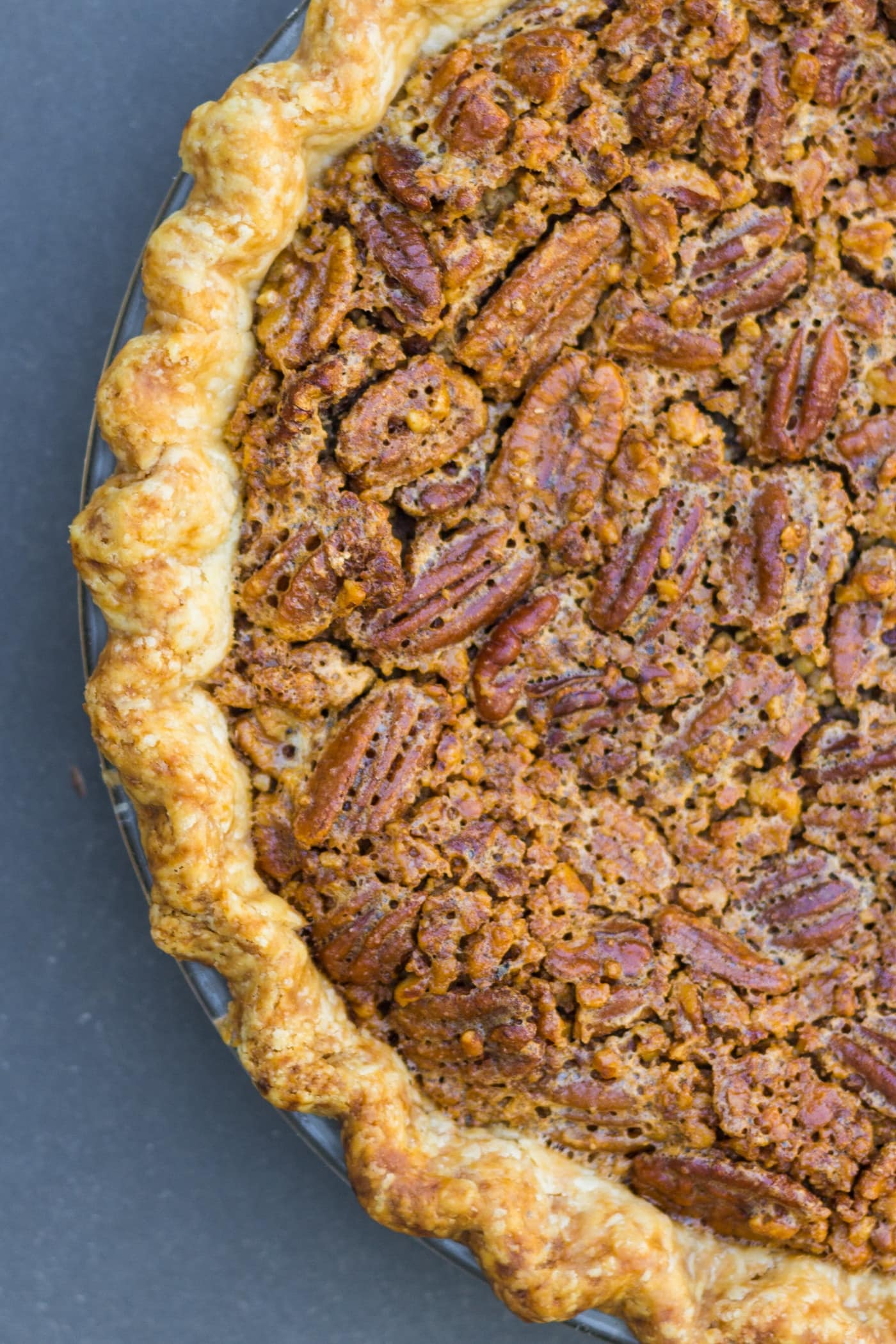 Top down view of pecan pie with pieces of pecans on top and browned crust all on blue slate surface