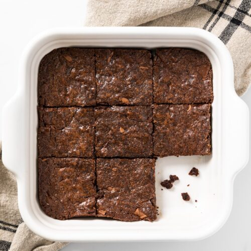 Top down view of brown colored brownies cut into squares sitting in a white baking pan all on white surface