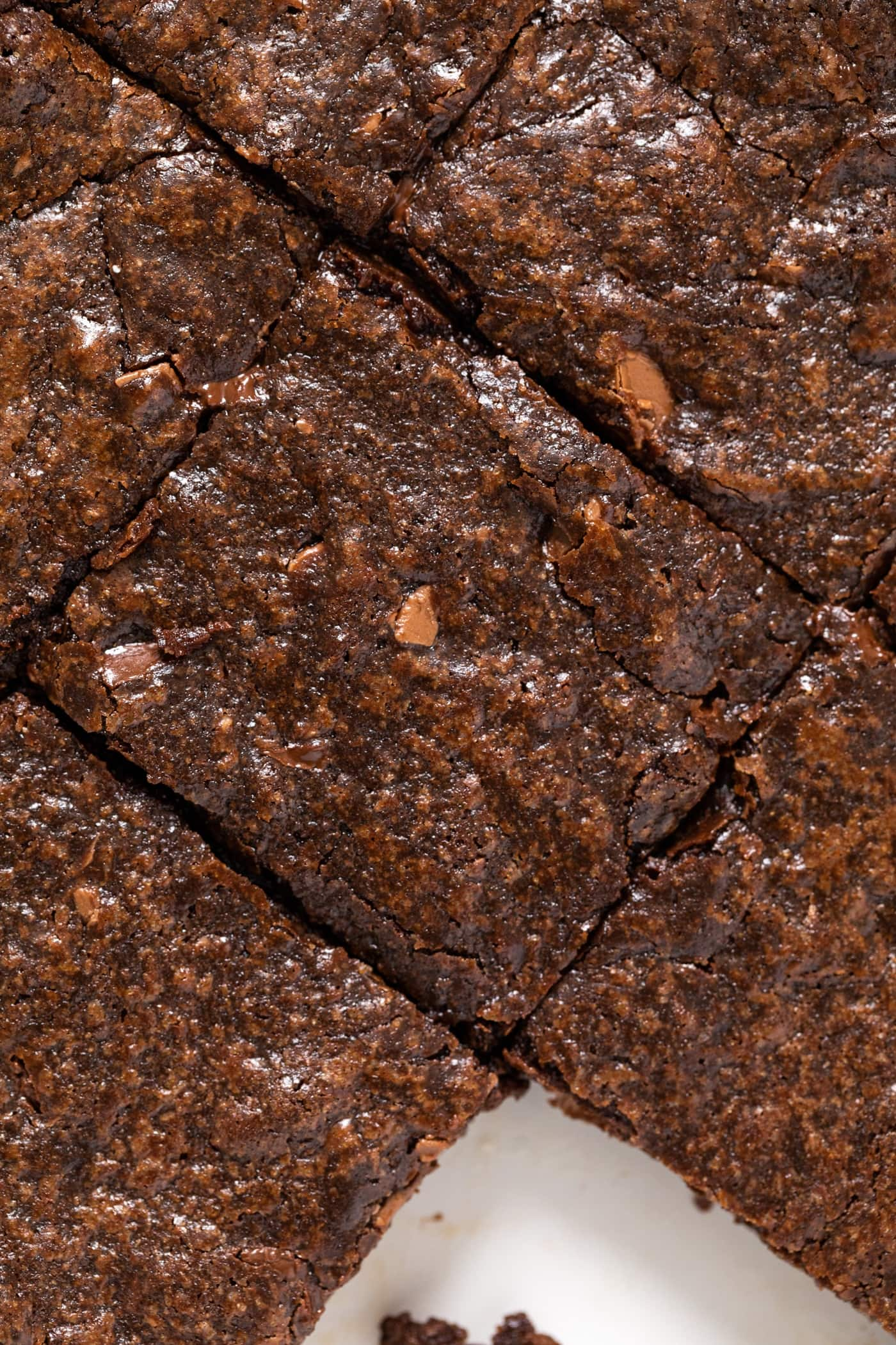 Top down close up view of chocolate brownie sitting amongst other brownies all in white pan