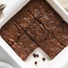 Top down view of white pan with baked brown colored brownies on white surface