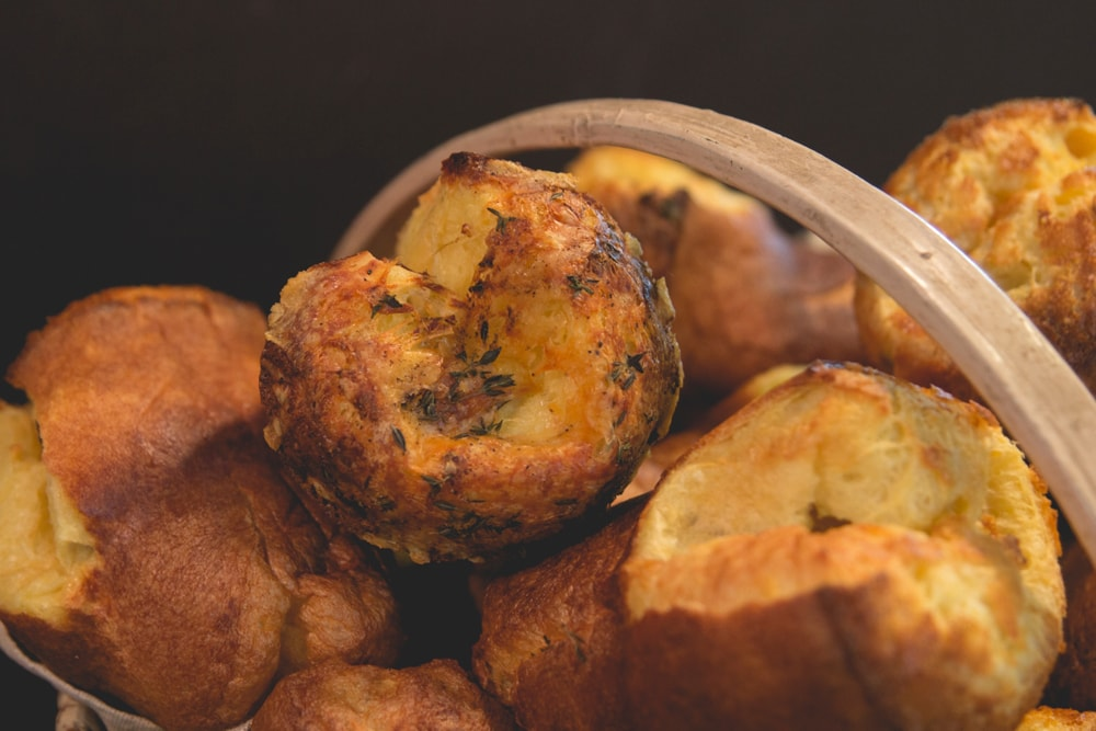Popovers piled on top of each other in a wood basket with some sprinkled with herbs all in front of a black background