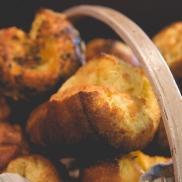 Multiple light brown popovers sitting on top of each other in wood basket with dark black background