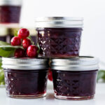 Three jars of canned cherry jam with extra cherries, leaves and additional cherry jam jars in background on a white surface