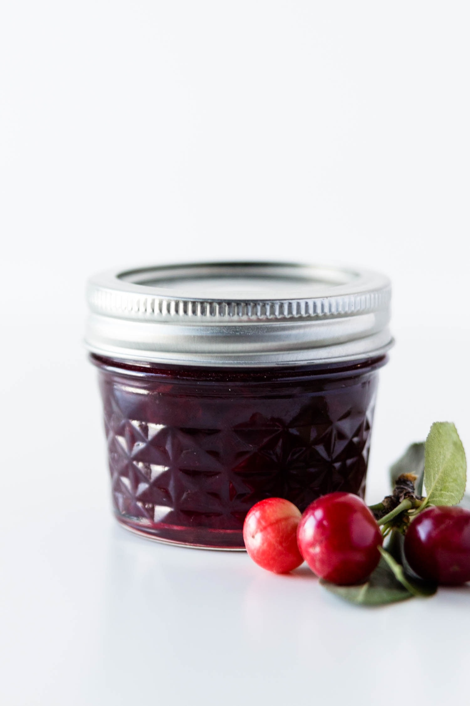 Jar of cherry jam with cherries in front on a white surface