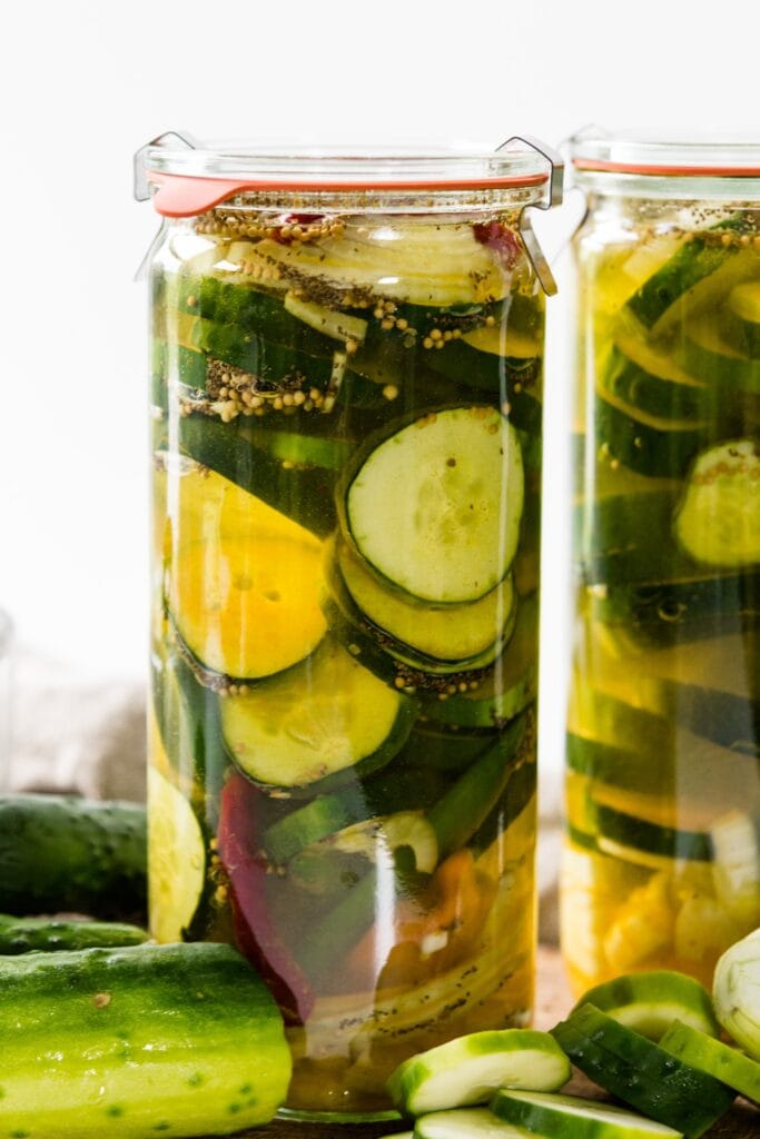 Glass jar of fridge pickles with cucumbers, onions, red peppers and celery seed in light yellow pickling liquid with cutting board and napkin in background
