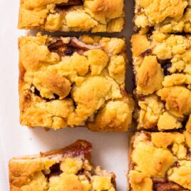 Top down view of squares of peach crumb bars sitting on white countertop with slices of peaches on cutting board