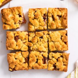 Top down view of nine peach crumb bars with golden top sitting on white countertop with sliced peaches around