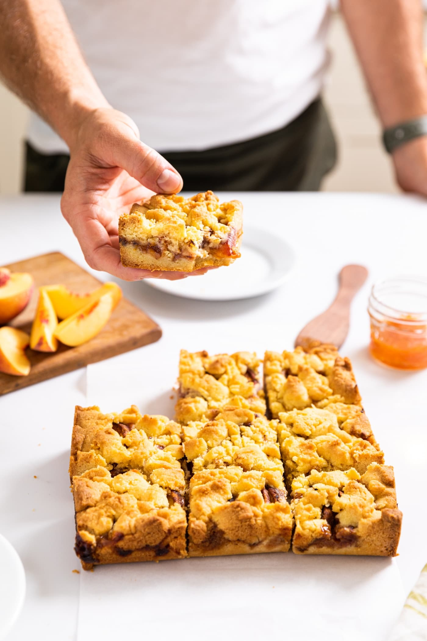 One hand holding single piece of a peach crumb bar with rest of bars sitting on white countertop below