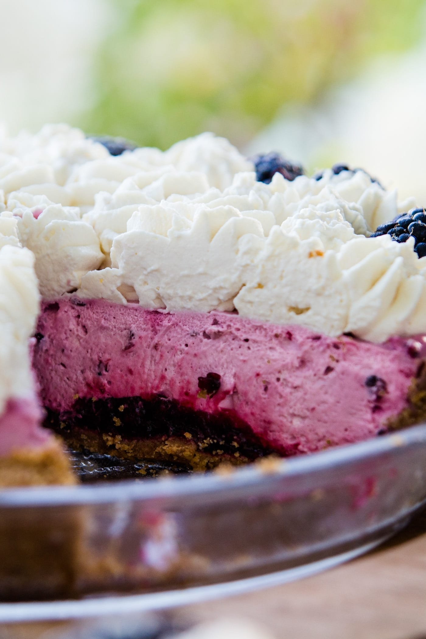 Blackberry icebox pie sitting on wood serving board with slice taken out showing the graham cracker crust layer, blackberry filling layer and whipped cream layer with who blackberries on top