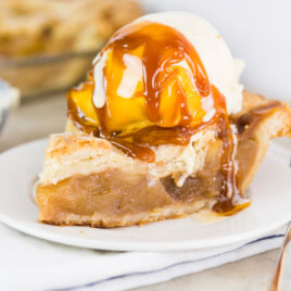 Scoop of ice cream sitting on slice of apple pie with caramel sauce drizzled over top sitting on white plate with napkin