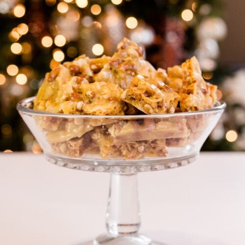 Golden peco candy with peanuts and flakes of coconut piled high in glass bowl on a white surface with Christmas lights in background