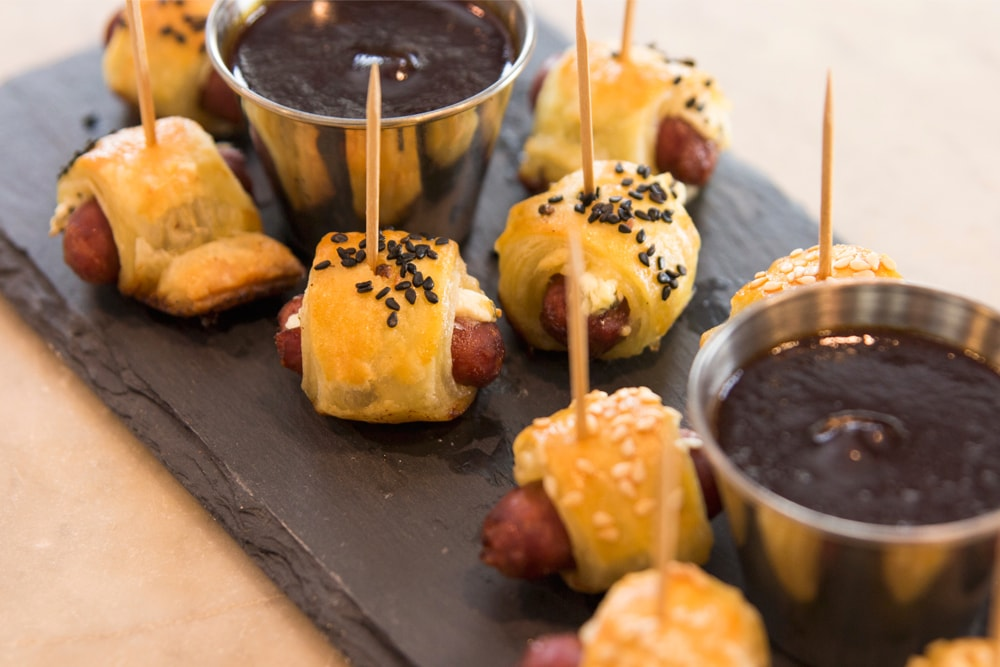 Pigs in a blanket wrapped in browned dough and topped with sesame seeds sitting on slate serving platter with barbecue sauce in steel container all on marble surface