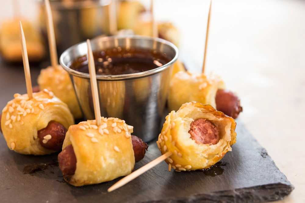 Little smoky hot dogs wrapped in dough with a bite missing with steel container in background holding barbecue sauce all on slate surface