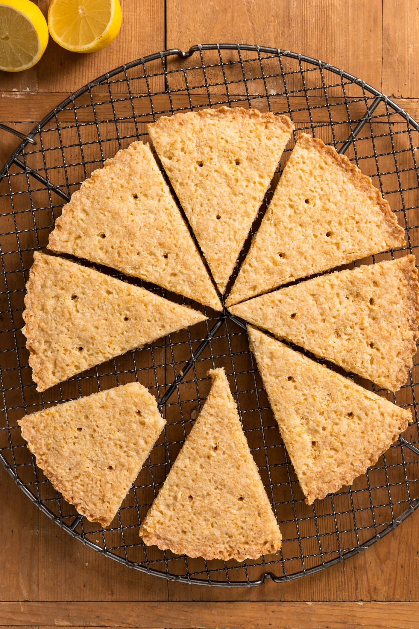 Top down view of triangle-shaped lemon shortbread cookies sitting on wire cooling rack all on wood surface