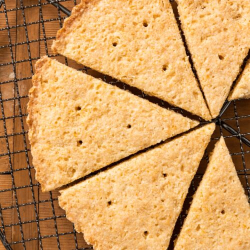 Top down view of golden colored cookies sitting on wire cooling rack all on wood surface