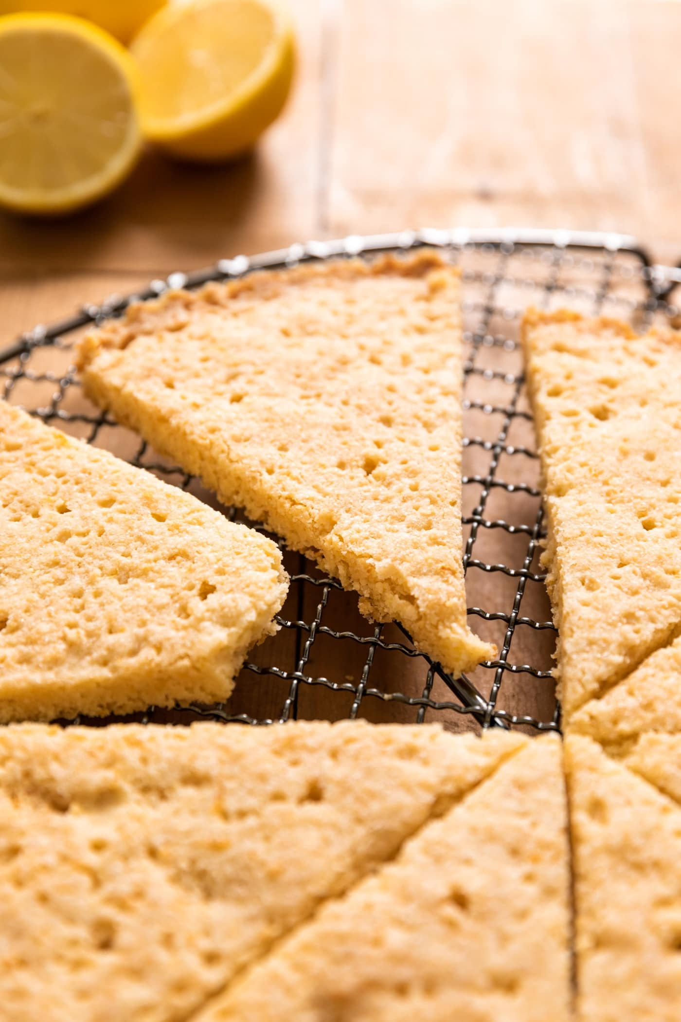 Triangle of golden colored lemon shortbread cookie sitting with other cookies on metal cooling rack with extra lemons in background