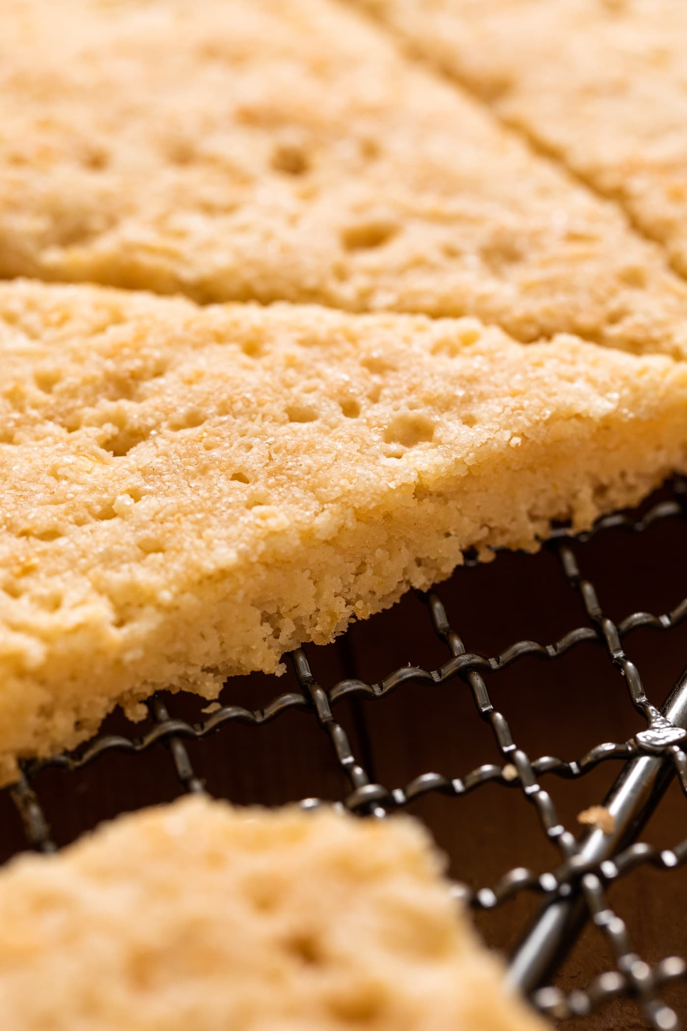 Close up view of golden colored lemon shortbread cookies sitting on metal cooling rack