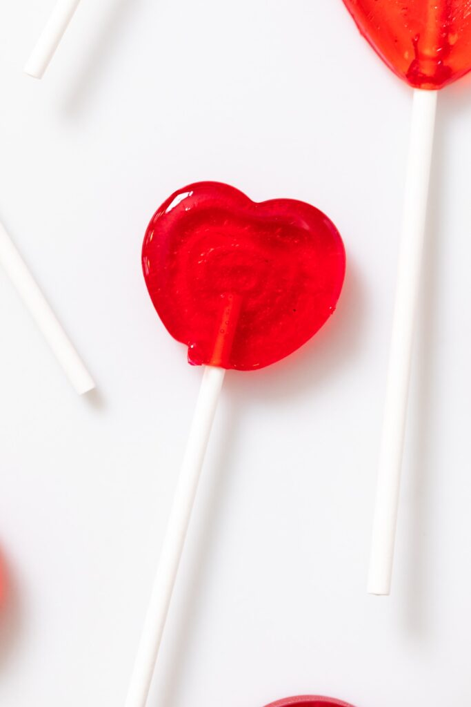Close up view of red heart-shaped cherry sucker sitting on white countertop with sucker sticks