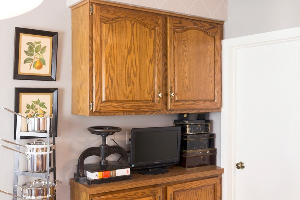 Cherry brown cabinets with television, cash boxes and weight sitting on kitchen countertop along with kitchen pot tree