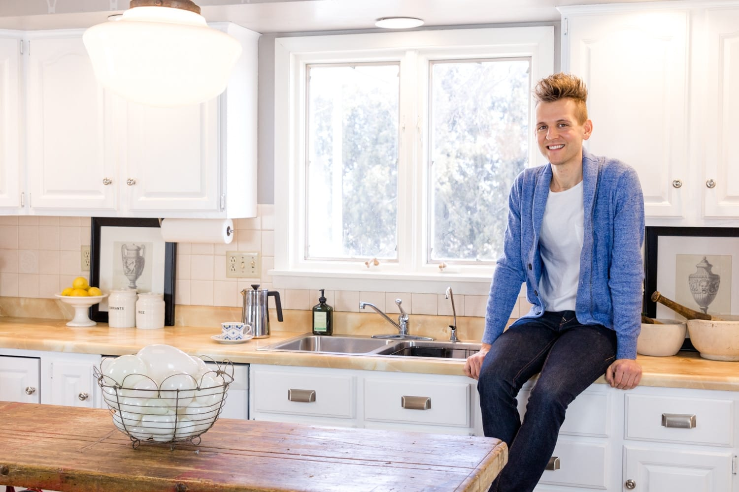 Kaleb Wyse sitting on countertop surrounded by fresh white cabinets after showing how to paint kitchen cabinets