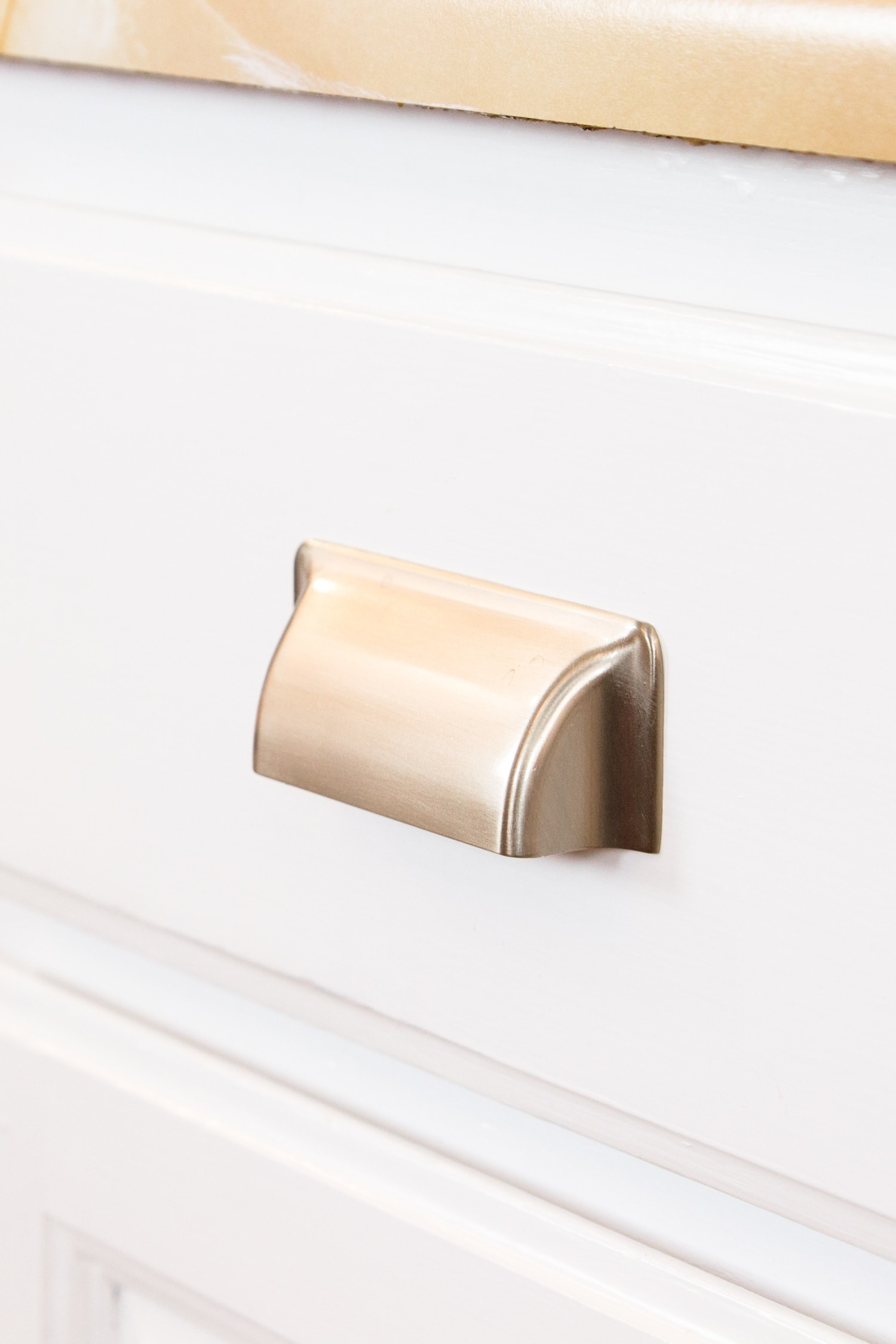 Matte silver drawer pulls attached to bright white lower kitchen cabinets