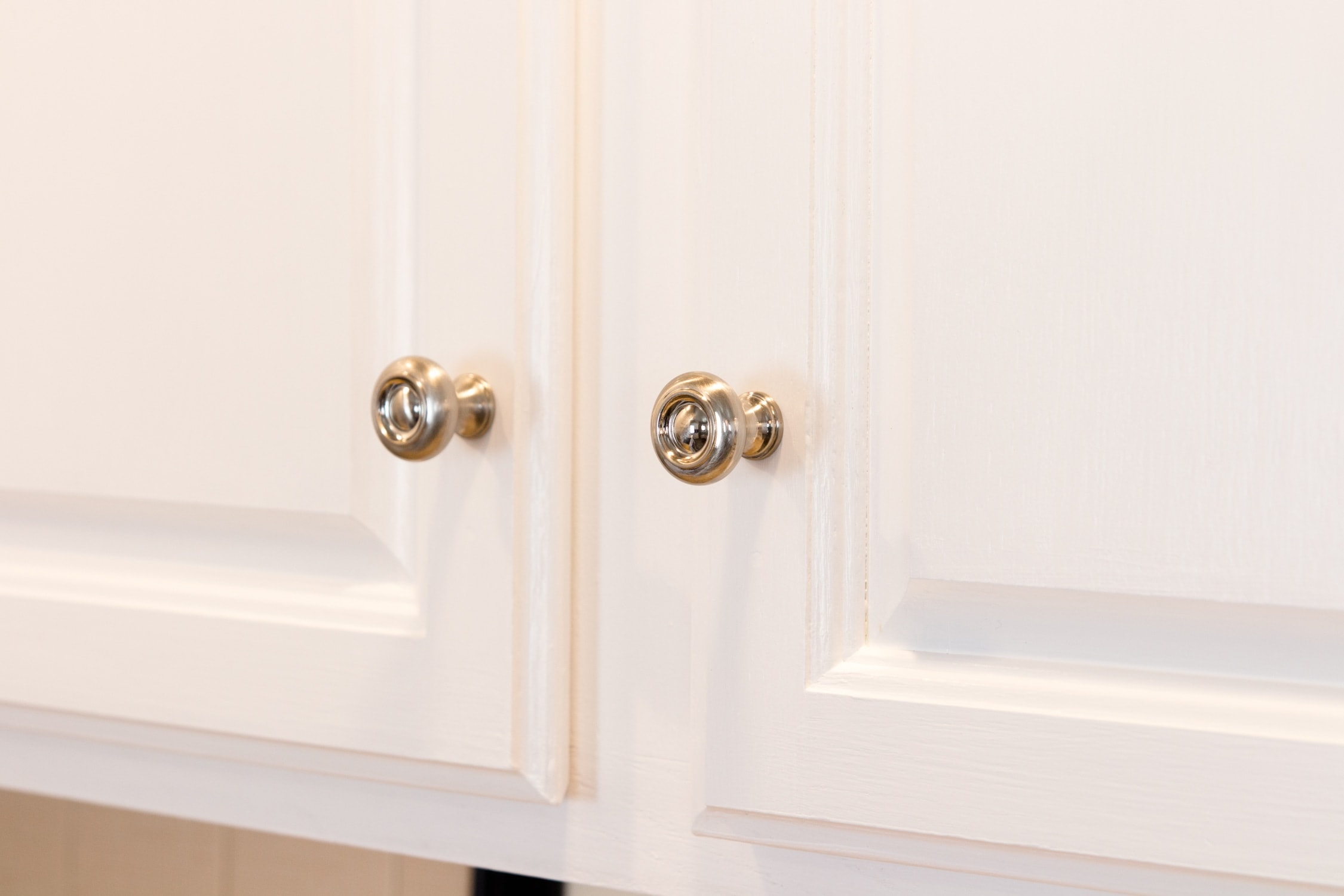 Close up view of silver pulls attached to bright white upper kitchen cabinets
