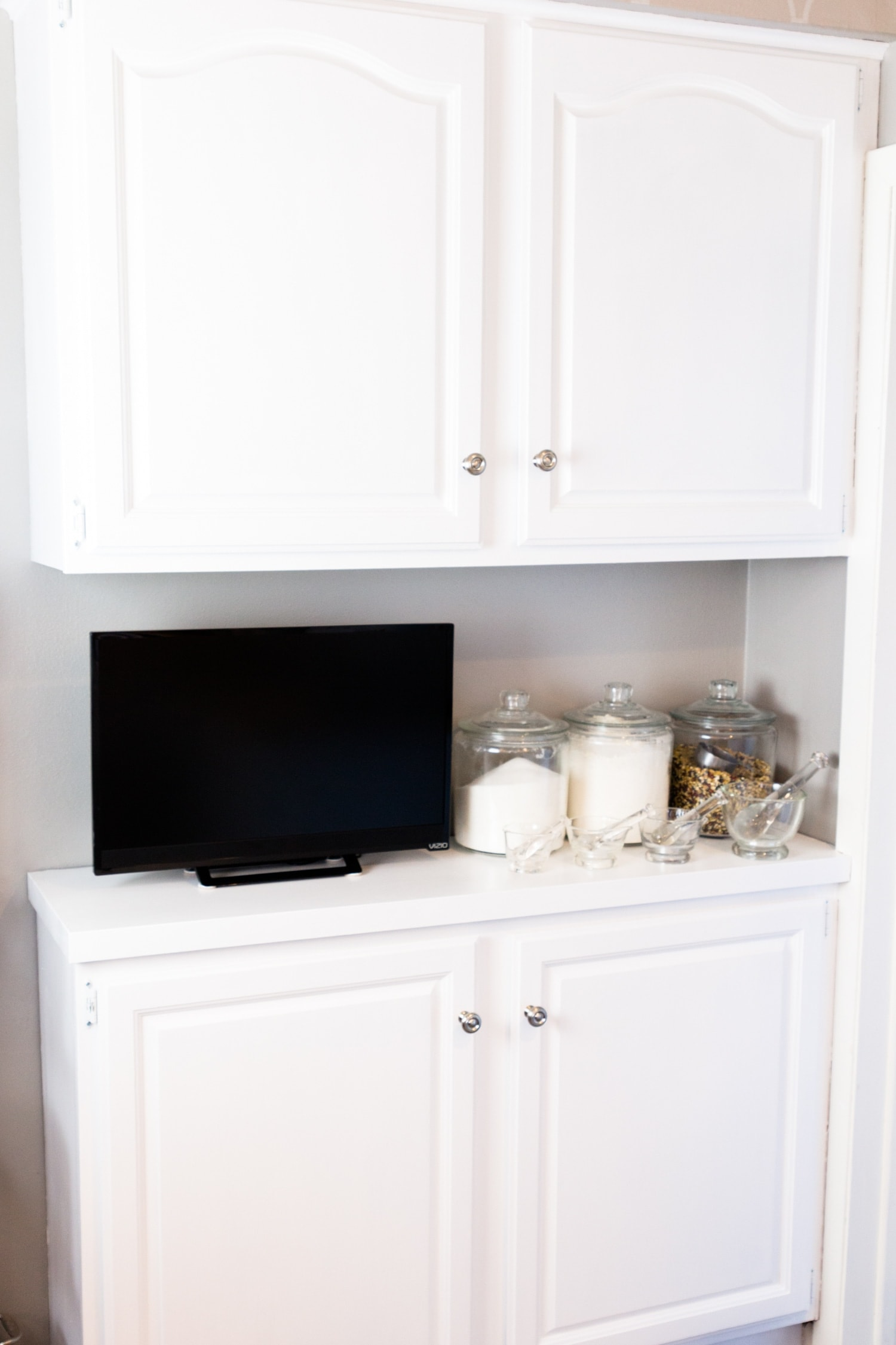 Bright white kitchen cabinets with television and jars full of kitchen supplies sitting on countertop