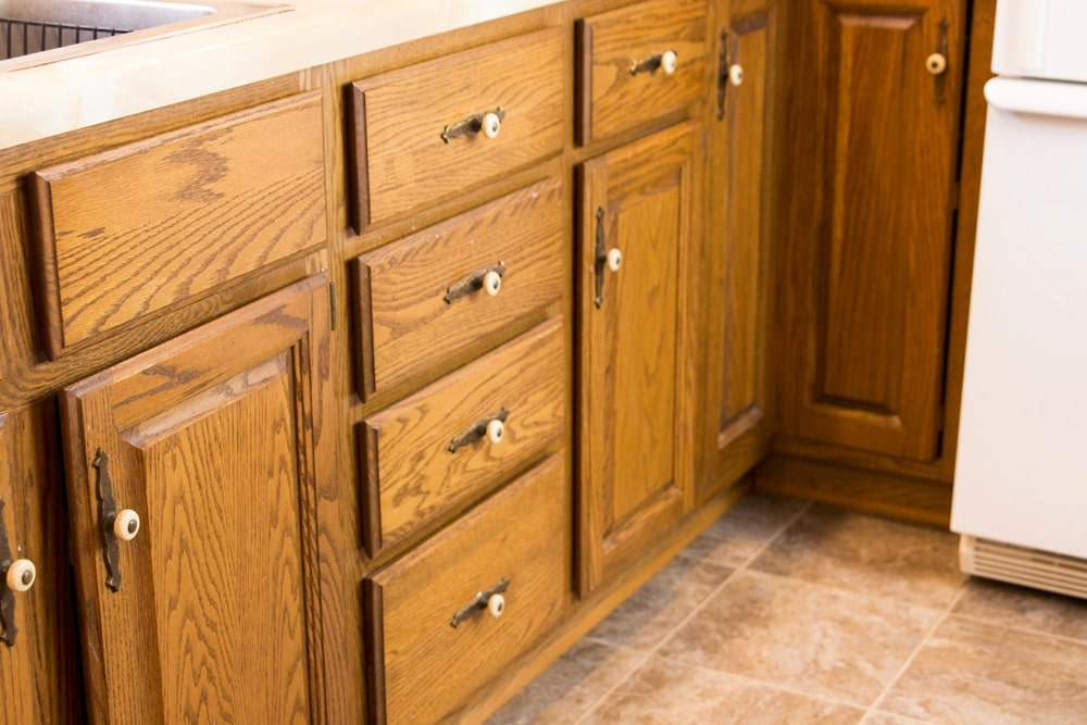 Cherry brown lower cabinets with pulls and knobs