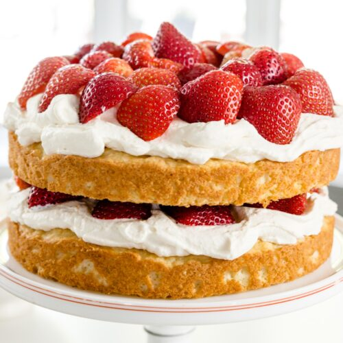 Strawberries, whipped cream and yellow cake in two layers on a white cake plate
