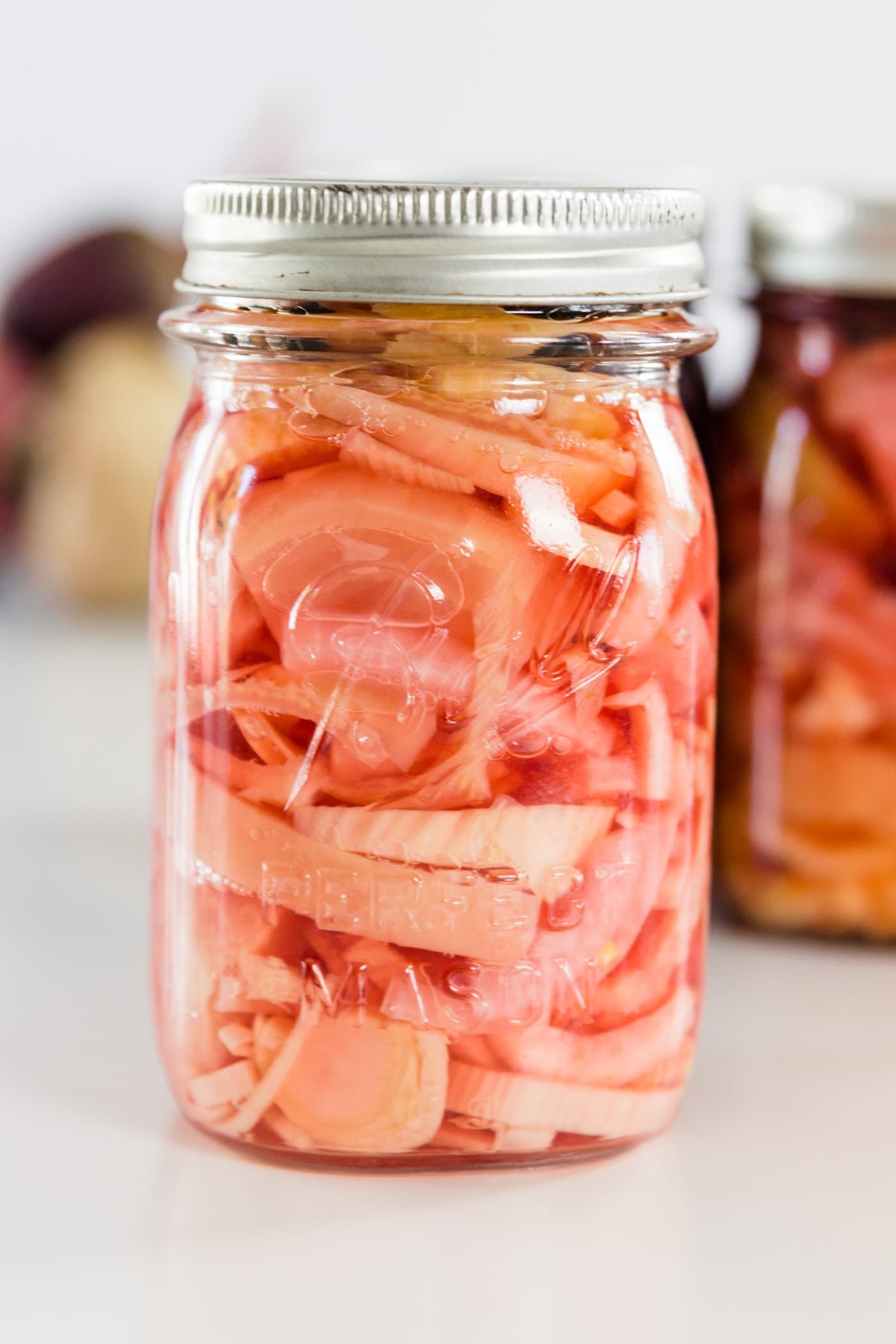 A white and pink canned beet recipe in a Ball canning jar on a white surface with Ball canning jars and beets in background.