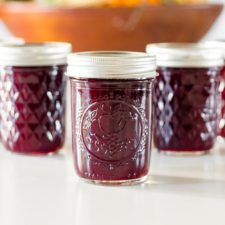 Five jam jars full of can grape butter with a brown bowl in background on a white surface