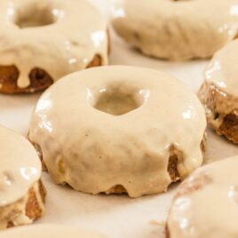 Pumpkin spice donuts sitting on piece of white parchment all on wood board