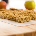 Apple pie bars sitting on a piece of parchment on a wood cutting board with apples in background
