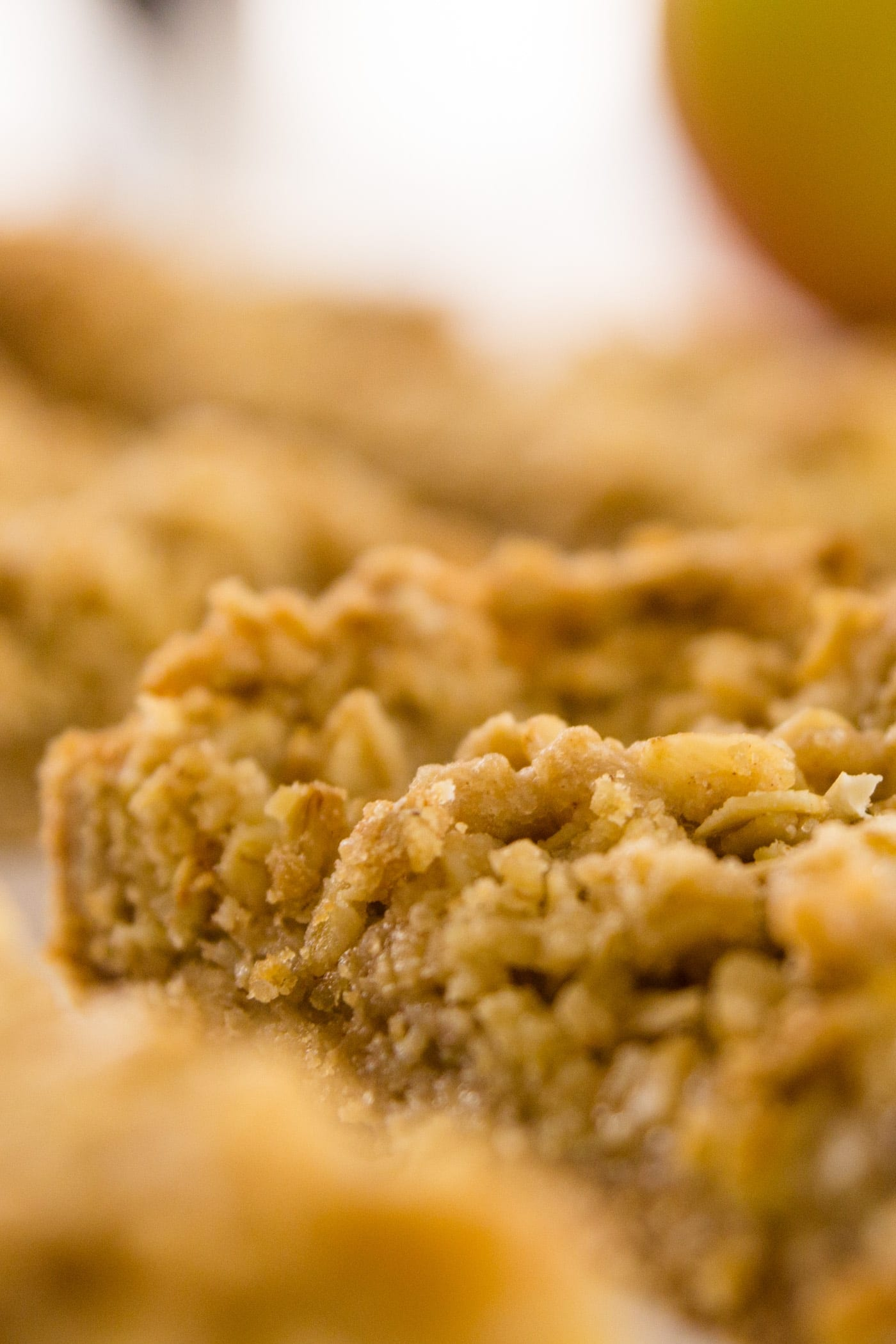 Close up of apple pie bars with crumble topping with apple in background