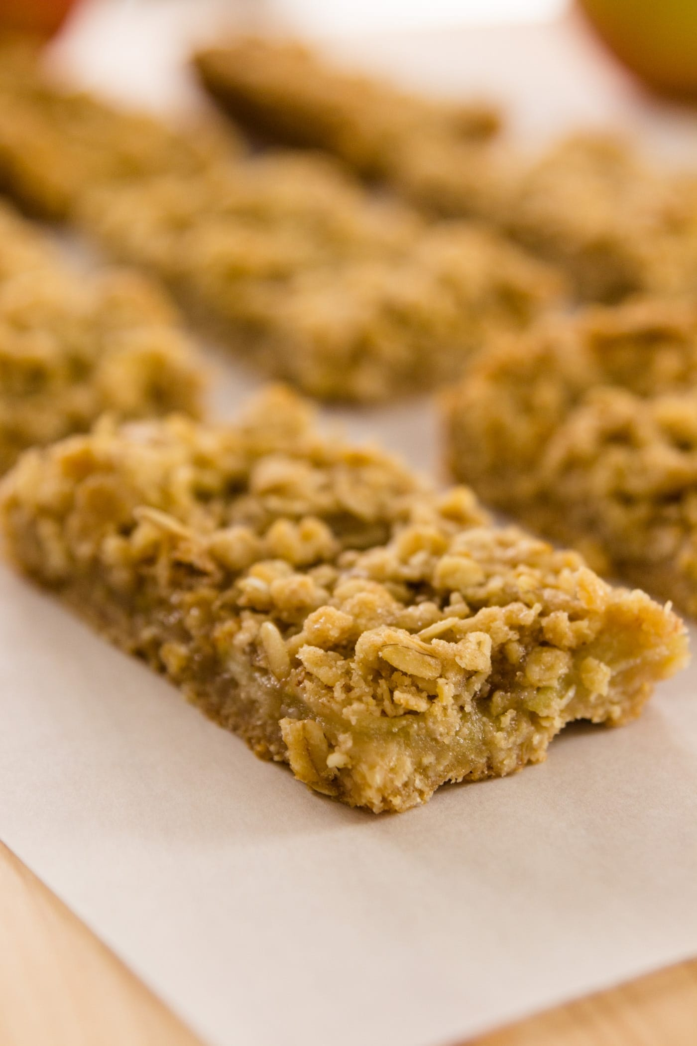 Apple pie bars sitting on piece of parchment on a wood cutting board with apples in background