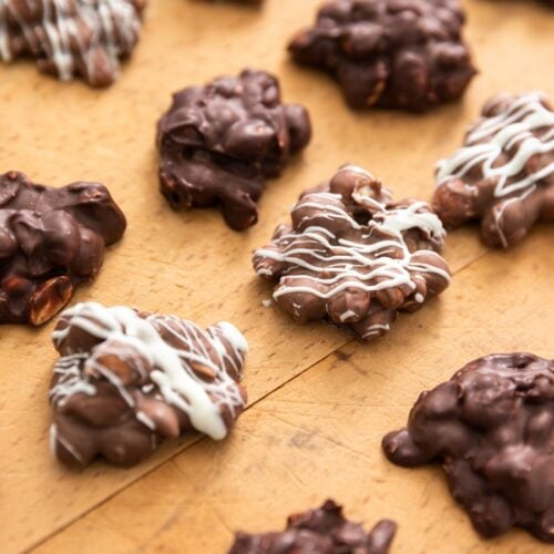 Chocolate peanut clusters sitting on wood board some drizzled with white chocolate