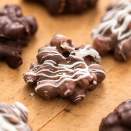 Chocolate peanut clusters topped with white chocolate sitting on wood surface