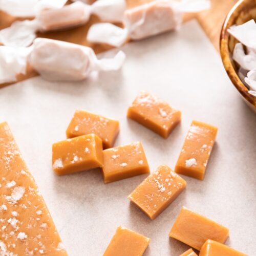 Pieces of golden cut caramel sitting on white piece of parchment paper with wrapped caramels in wax paper in background