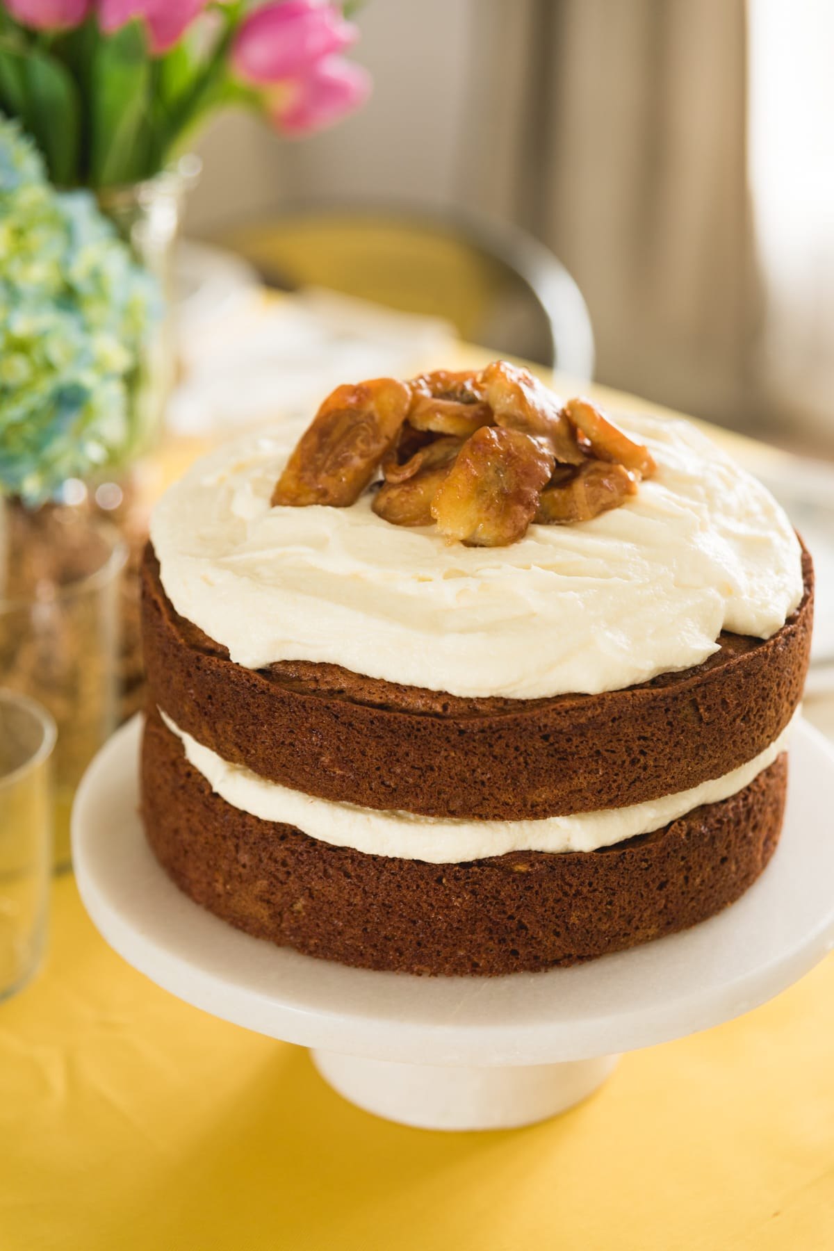 Brown butter banana cake topped with white frosting topped with bananas sitting on white cake plate all on yellow tablecloth
