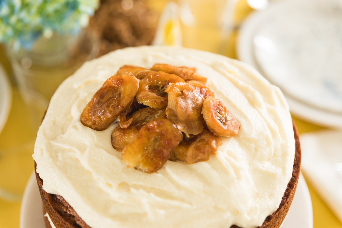 Top down view of two layer brown butter banana cake topped with white frosting and cooked bananas on white cake plate all on yellow tablecloth