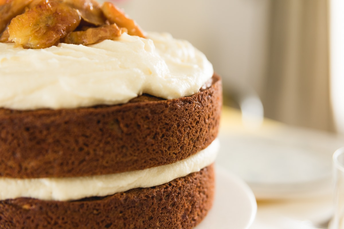Close up view of side of two layer cake topped with white frosting on white cake plate