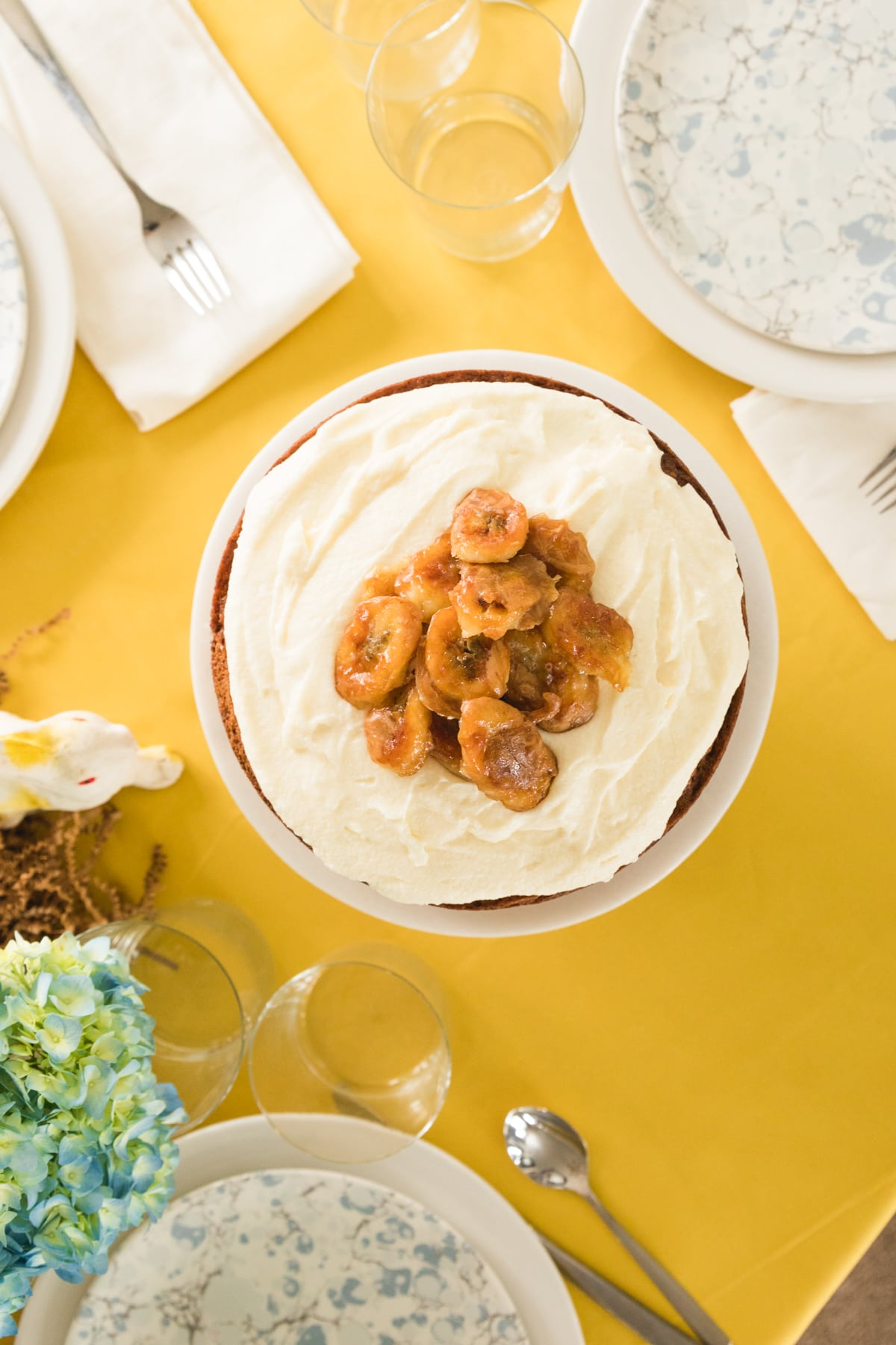 Top down view of cake topped with white frosting and cooked bananas all on yellow tablecloth set with place settings