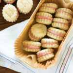 Top down view of rhubarb wafer cookies with light pink filling sitting in a parchment lined treat box one top of white dish towel
