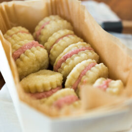 Rhubarb wafer cookies with light pink filling sitting in parchment lined white rectangular box on top of white towel on wood bread board