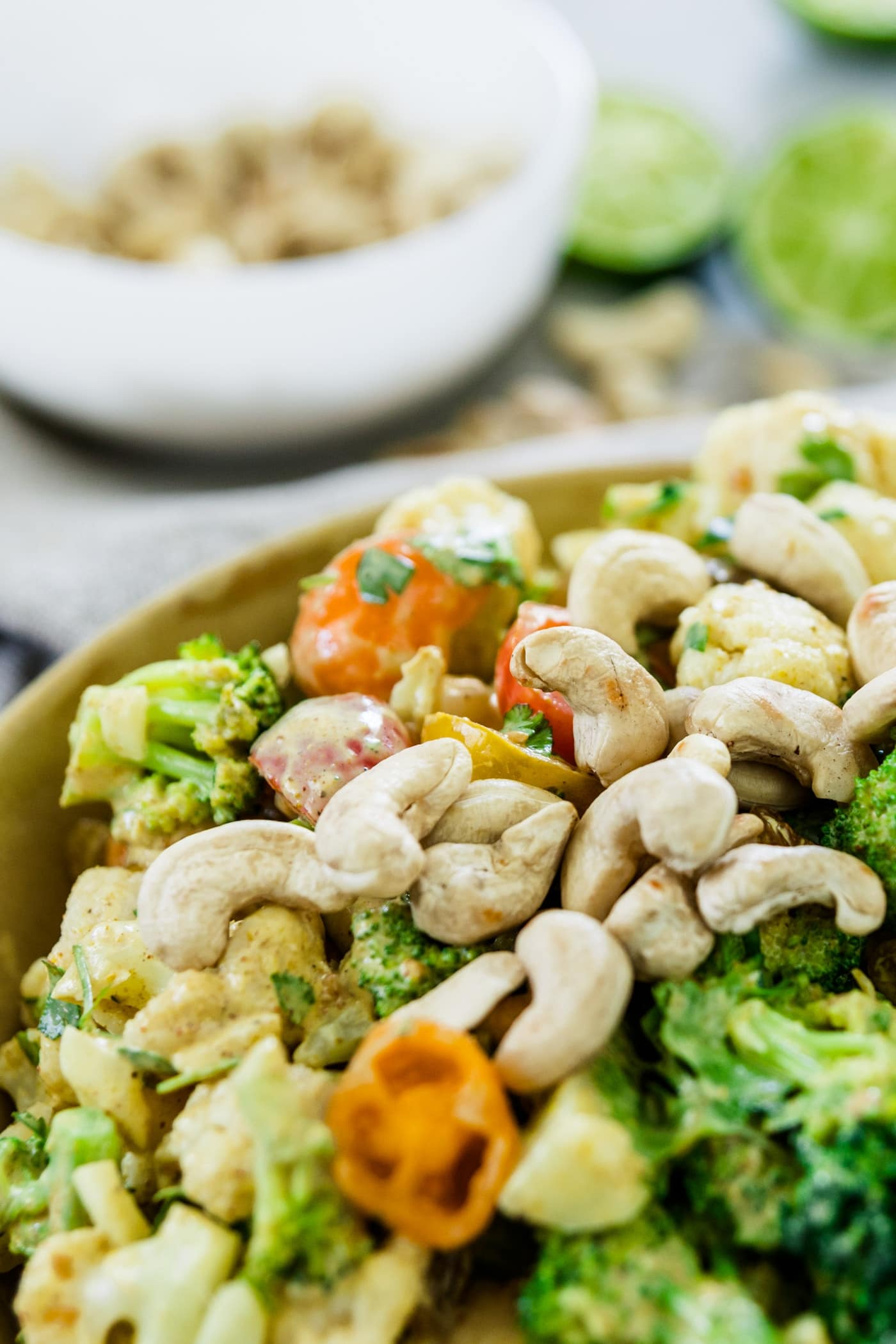Pieces of broccoli, tomatoes and cauliflower salad in a large yellow bowl sprinkled with cashews with used limes and extra cashews in a bowl in background on a marble surface