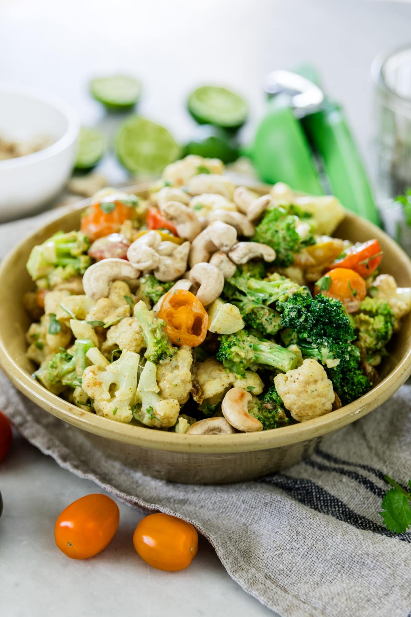 Pieces of broccoli, tomatoes and cauliflower salad in a large yellow bowl sprinkled with cashews with used limes, extra cashews in a bowl, a lime squeezer and napkin in background on a marble surface
