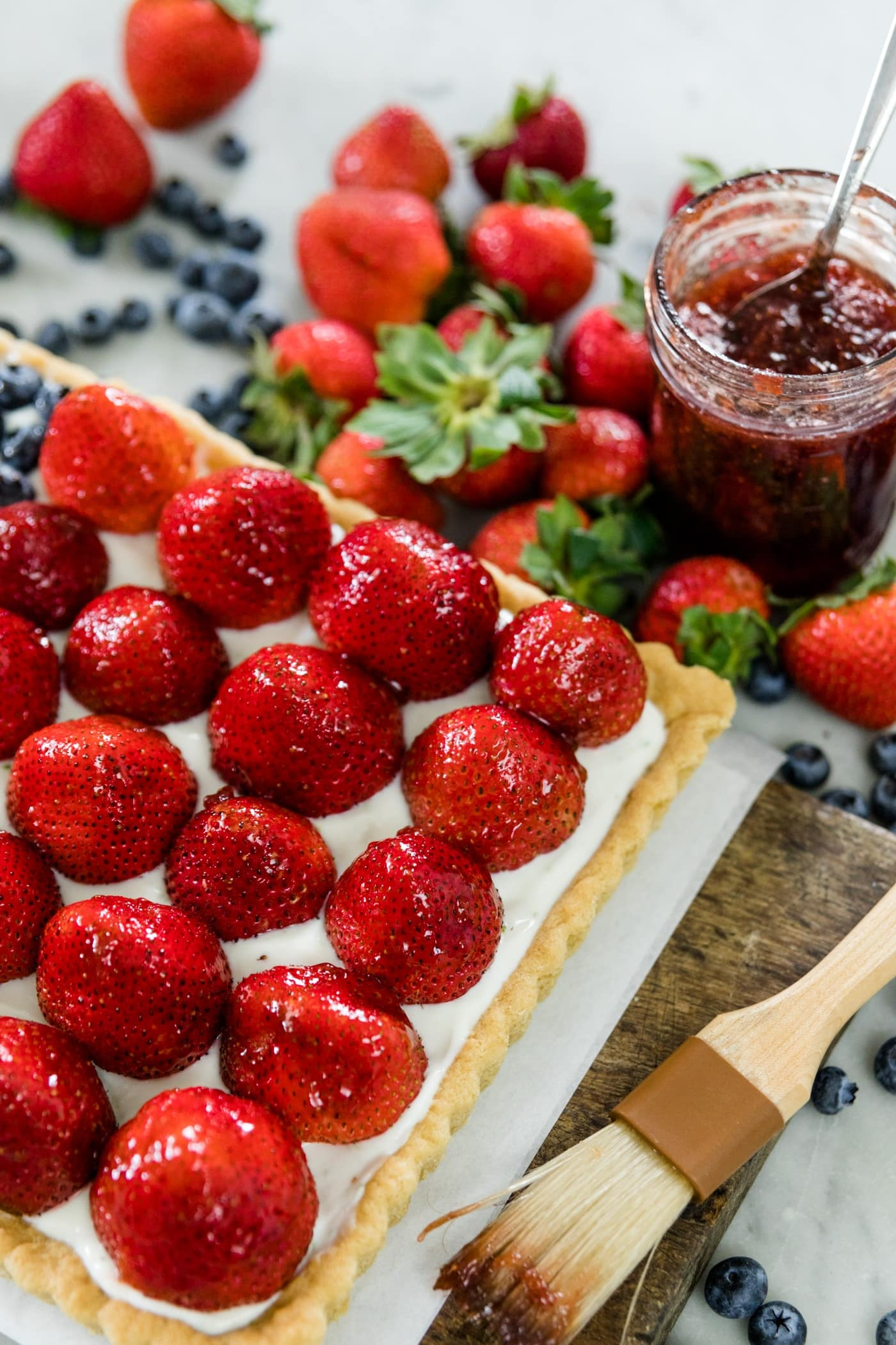 Strawberries and blueberries on a cookie tart with yogurt filling with extra strawberries, blueberries and jam in background on a wood cutting board on a marble surface
