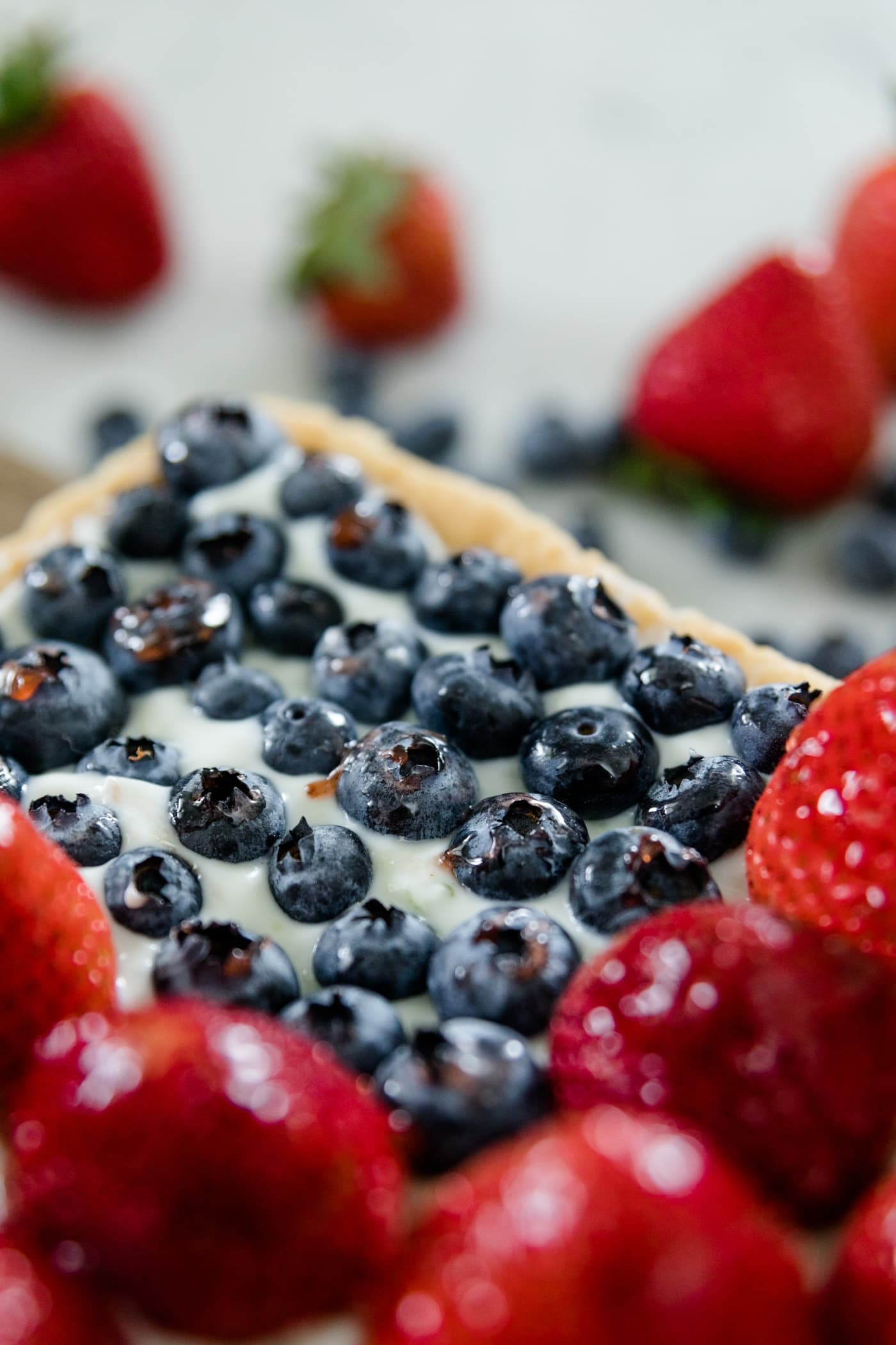 Strawberries and blueberries on a cookie tart with yogurt filling with extra strawberries and blueberries in background on a marble surface